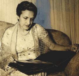 Cecília Meireles sentada vendo um álbum de fotos